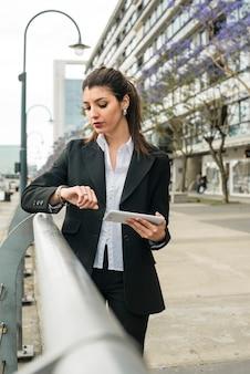 Ritratto di un telefono cellulare della tenuta della giovane donna di affari che controlla il tempo sul suo orologio da polso