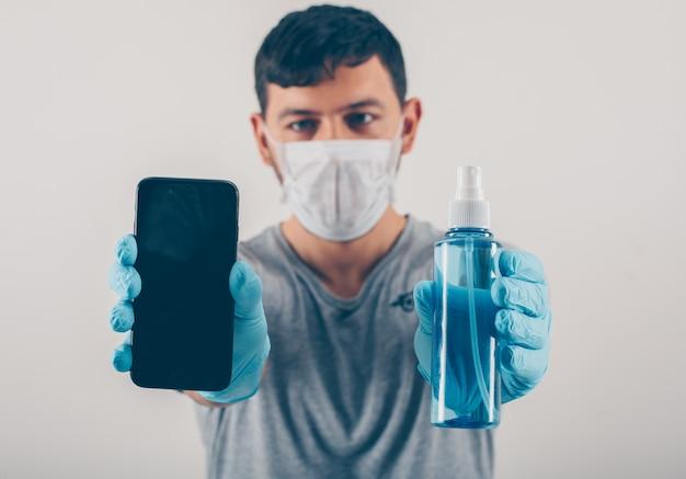 Ritratto di un uomo a sfondo chiaro in possesso di un telefono e disinfettante per le mani in guanti e maschera medica