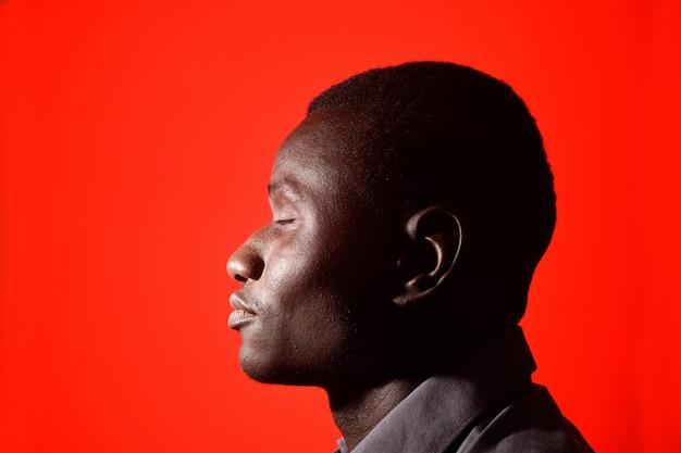 Ritratto di un uomo africano con gli occhi chiusi su sfondo rosso