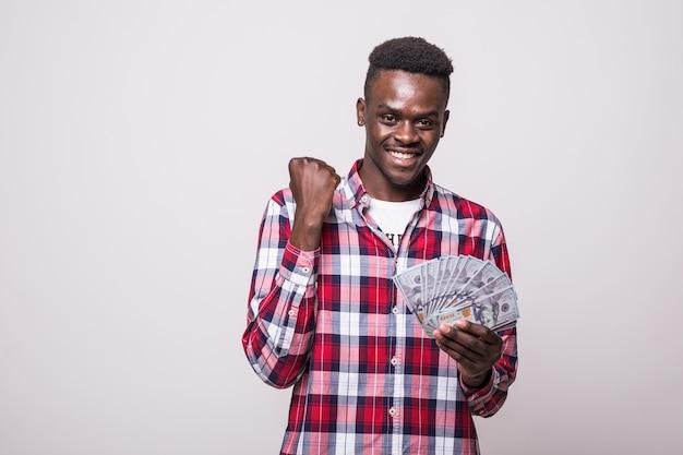 Ritratto di un uomo africano emozionante felice che tiene mazzo di banconote di soldi e che sembra isolato