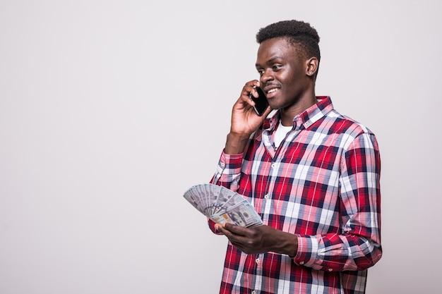 Ritratto di un uomo africano soddisfatto eccitato che tiene un mazzo di banconote di denaro mentre parla al telefono cellulare e sembra isolato