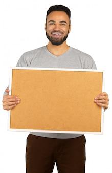 Ritratto di un uomo afro americano felice che tiene scheda in bianco isolata su un bianco