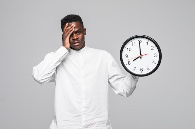 Ritratto di un uomo afroamericano che tiene l'orologio assonnato della parete alle 7 di mattina isolato su una priorità bassa bianca