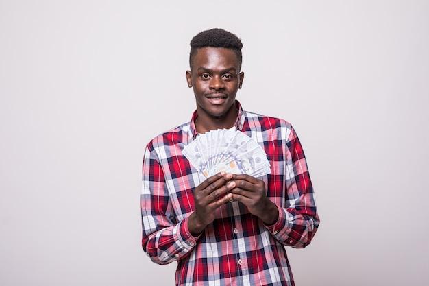Ritratto di un uomo afroamericano eccitato gioioso che tiene le banconote dei soldi e che sembra isolato
