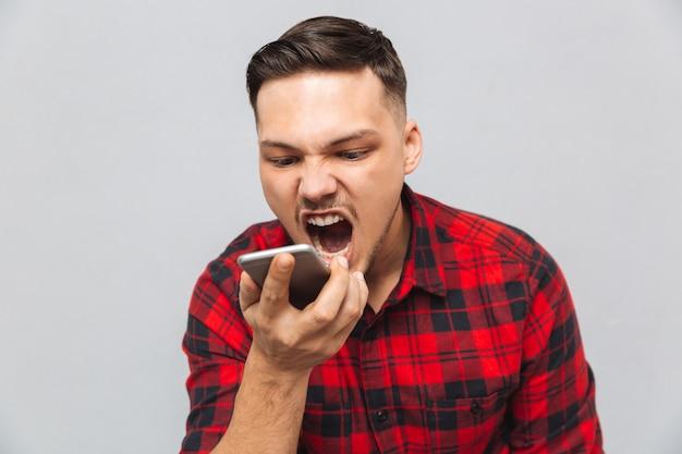 Ritratto di un uomo aggressivo in camicia a quadri da vicino