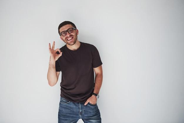 Ritratto di un uomo allegro in maglietta e occhiali da vista e mostrando il segno ok