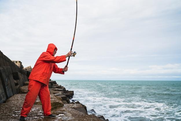 Ritratto di un uomo anziano che pesca sugli scogli al mare. concetto di pesca.