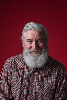 Ritratto di un uomo anziano con la barba grigia che guarda alla macchina fotografica contro il contesto rosso