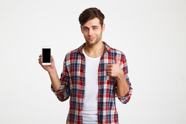 Ritratto di un uomo attraente sorridente che tiene telefono cellulare in bianco