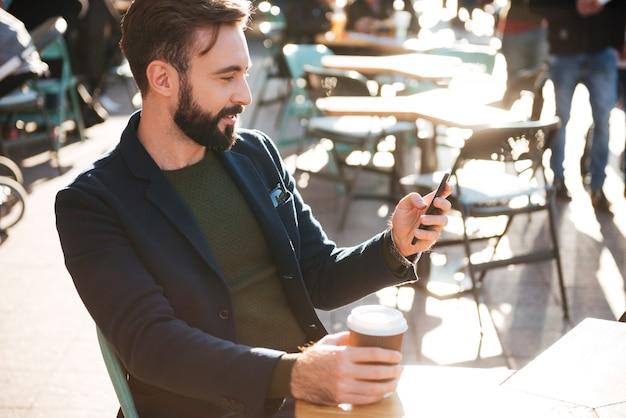 Ritratto di un uomo barbuto alla moda che per mezzo del telefono cellulare