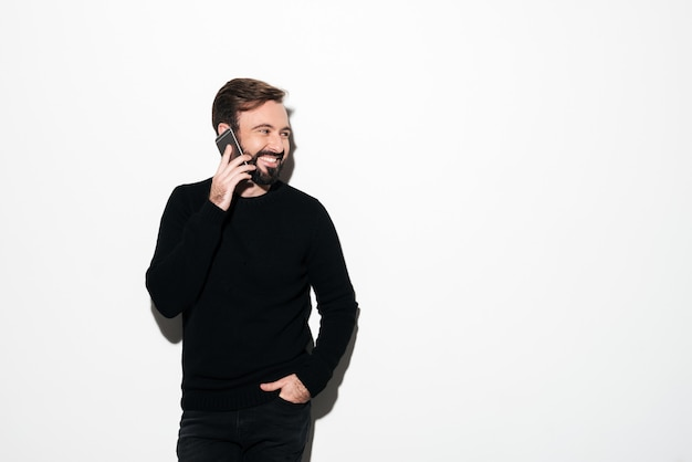 Ritratto di un uomo barbuto allegro che parla sul telefono cellulare
