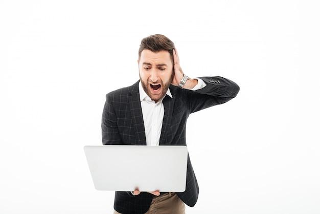 Ritratto di un uomo barbuto arrabbiato che tiene computer portatile