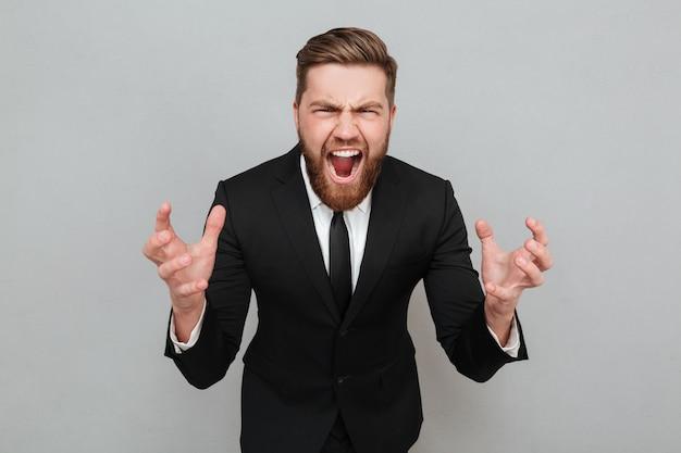 Ritratto di un uomo barbuto arrabbiato in tuta gridando