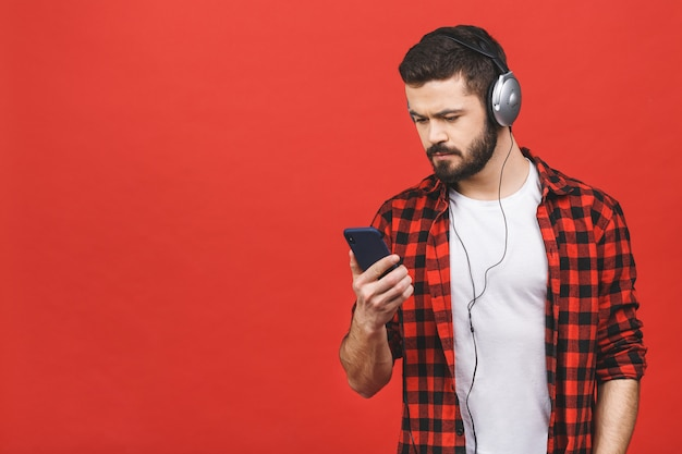 Ritratto di un uomo barbuto attraente bello con le cuffie che giudicano telefono cellulare isolato.