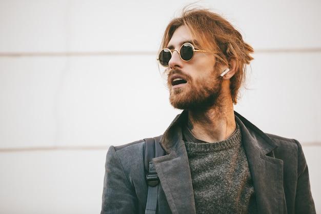 Ritratto di un uomo barbuto attraente che indossa occhiali da sole