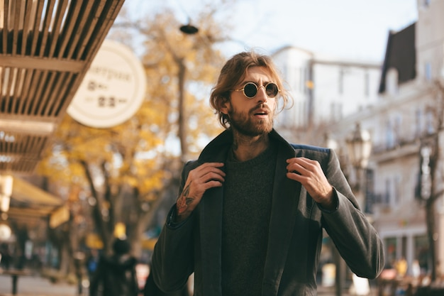Ritratto di un uomo barbuto bello che indossa occhiali da sole