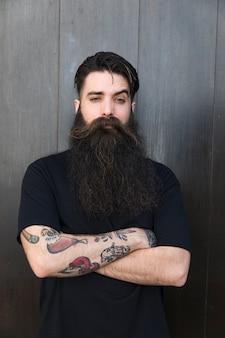 Ritratto di un uomo barbuto che attraversa le sue braccia contro il muro nero