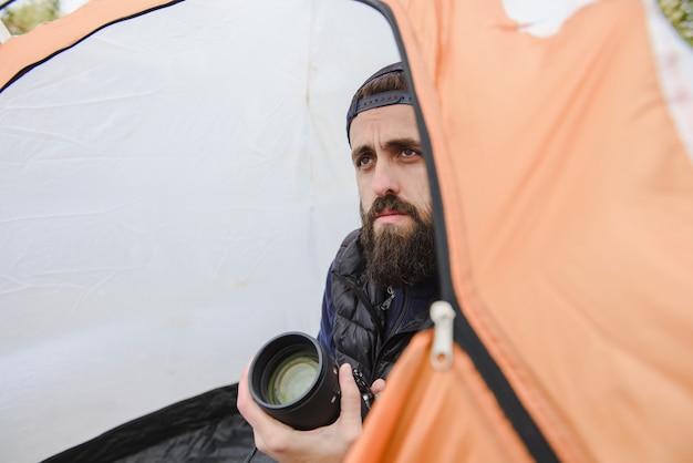 Ritratto di un uomo barbuto con una macchina fotografica