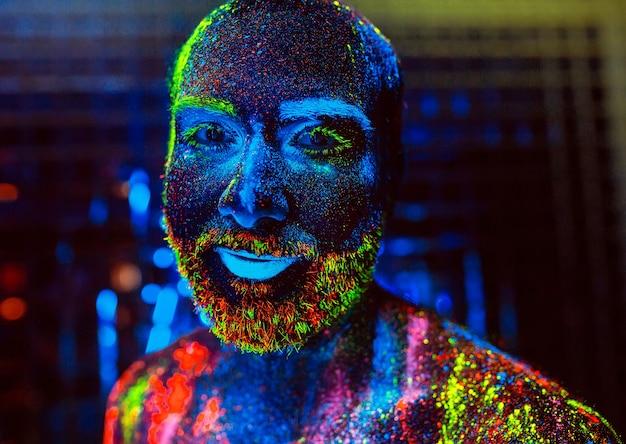 Ritratto di un uomo barbuto dipinto in polvere fluorescente.