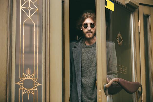 Ritratto di un uomo barbuto elegante vestito in cappotto che esce