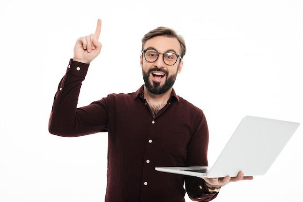 Ritratto di un uomo barbuto emozionante che tiene computer portatile