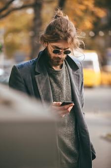 Ritratto di un uomo barbuto fiducioso in occhiali da sole