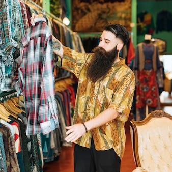 Ritratto di un uomo barbuto guardando la camicia a quadri nel negozio di abbigliamento