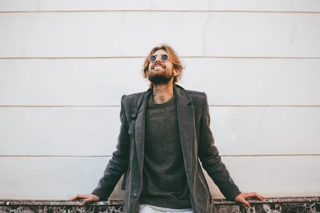 Ritratto di un uomo barbuto sorridente che indossa occhiali da sole