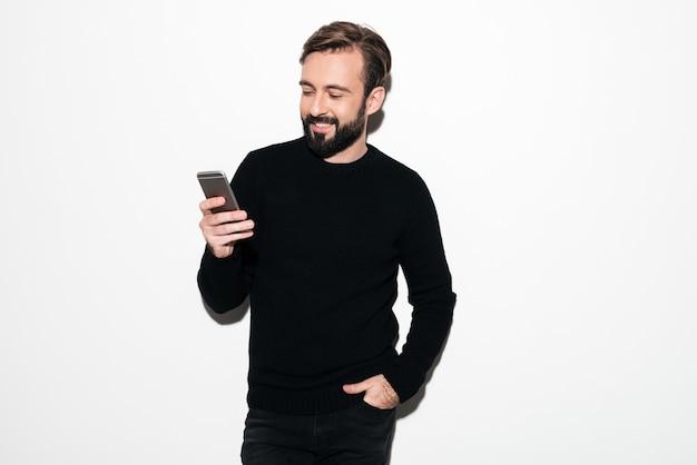 Ritratto di un uomo barbuto sorridente che manda un sms sul telefono cellulare