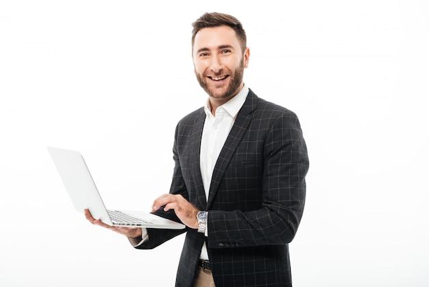 Ritratto di un uomo barbuto sorridente che tiene computer portatile