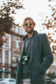 Ritratto di un uomo barbuto sorridente con la macchina fotografica