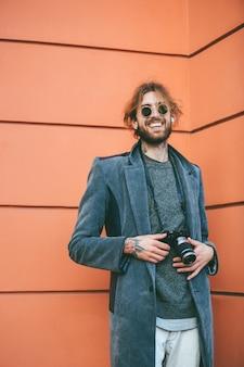 Ritratto di un uomo barbuto sorridente con macchina fotografica d'epoca