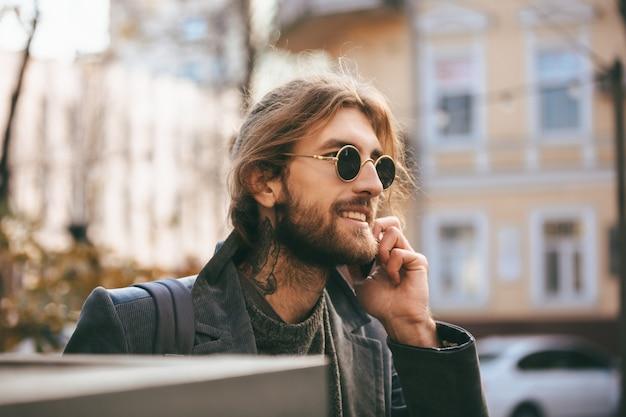 Ritratto di un uomo barbuto sorridente in occhiali da sole