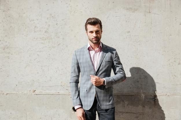 Ritratto di un uomo bello serio in una giacca in piedi