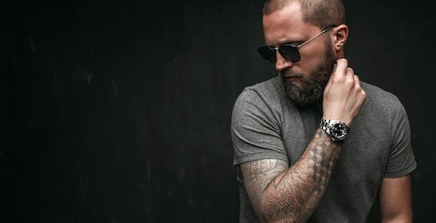 Ritratto di un uomo calvo bello con la barba lunga ben rifinita che indossa occhiali da sole e camicia grigia che osserva via al lato