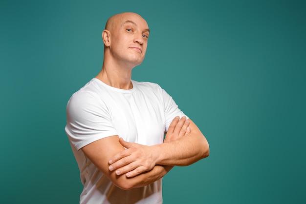 Ritratto di un uomo calvo emotivo in una maglietta bianca su sfondo blu.