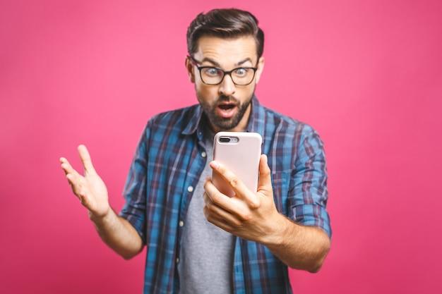 Ritratto di un uomo casual sorpreso guardando il telefono cellulare