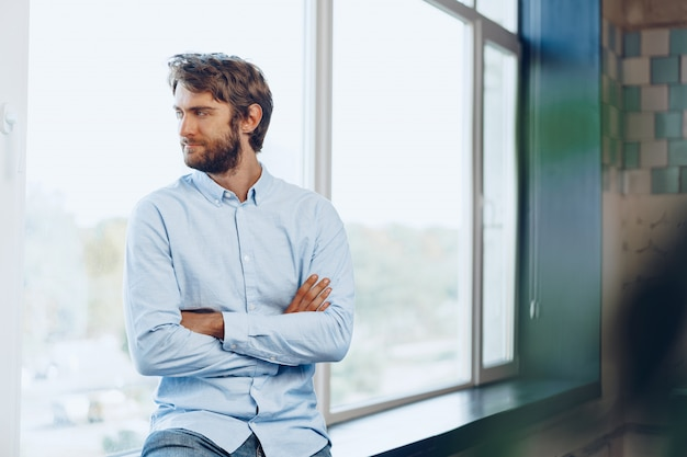 Ritratto di un uomo caucasico in camicia casual in piedi vicino alla finestra. ritratto di uomo d'affari
