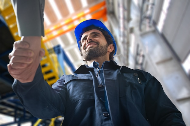 Ritratto di un uomo che dà una stretta di mano in una struttura industriale