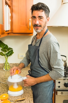 Ritratto di un uomo che fa il succo d'arancia in cucina