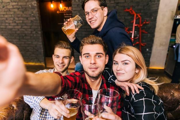 Ritratto di un uomo che prende selfie sul cellulare con il suo amico