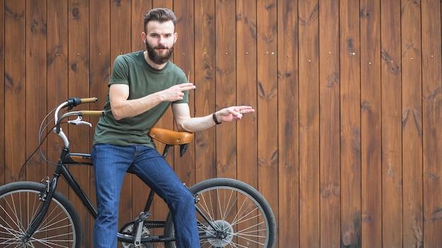 Ritratto di un uomo che si siede sulla bicicletta che fa gesto di mano
