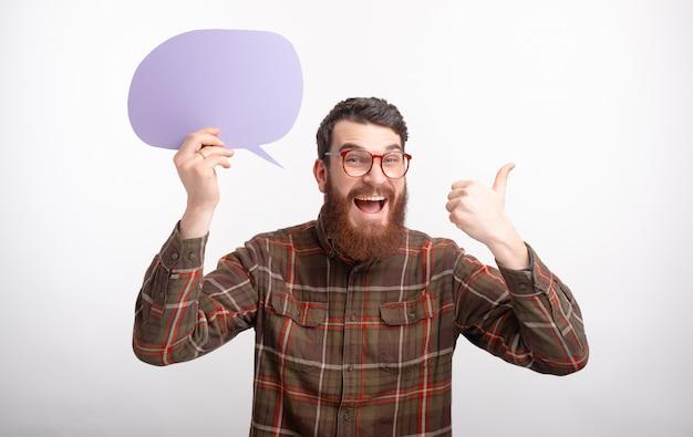 Ritratto di un uomo che tiene un discorso viola della bolla e che mostra pollice su su fondo bianco.