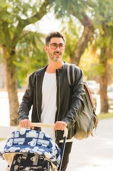 Ritratto di un uomo con il suo zaino a piedi con carrozzina nel parco
