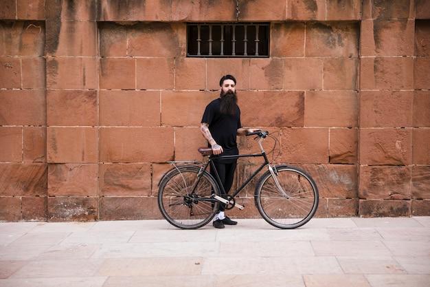Ritratto di un uomo con la bicicletta in piedi davanti al muro rosso