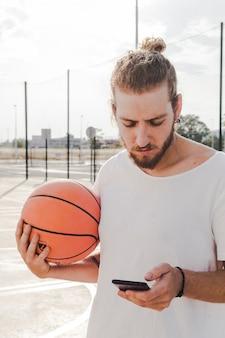 Ritratto di un uomo con la pallacanestro tramite cellulare