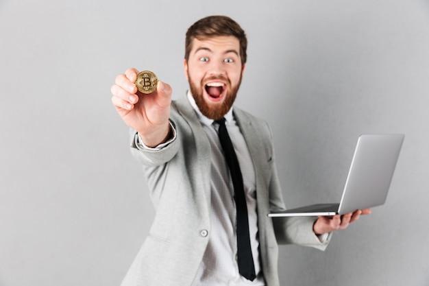 Ritratto di un uomo d'affari allegro che mostra bitcoin