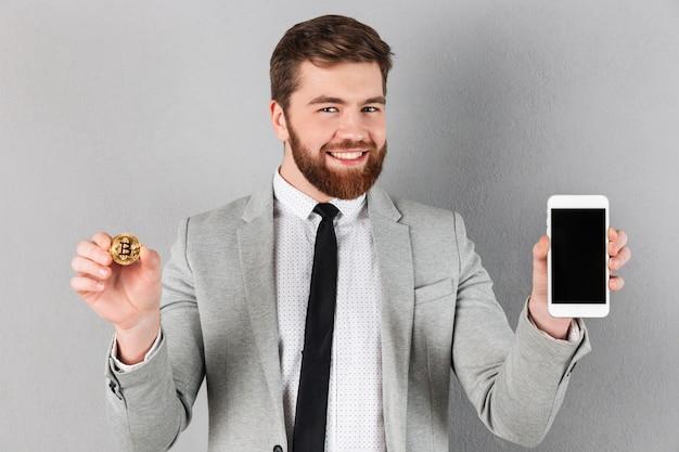 Ritratto di un uomo d'affari allegro che tiene bitcoin