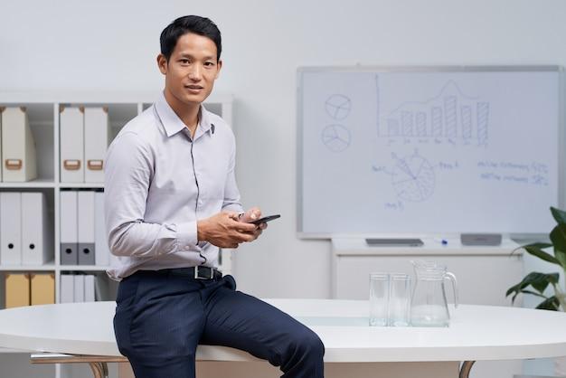 Ritratto di un uomo d'affari asiatico che si siede sulla scrivania che manda un sms sul suo telefono