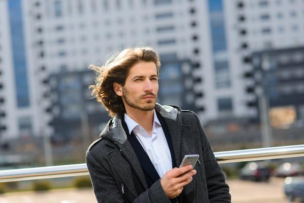 Ritratto di un uomo d'affari bello con il telefono, tazza di caffè nelle strade della città